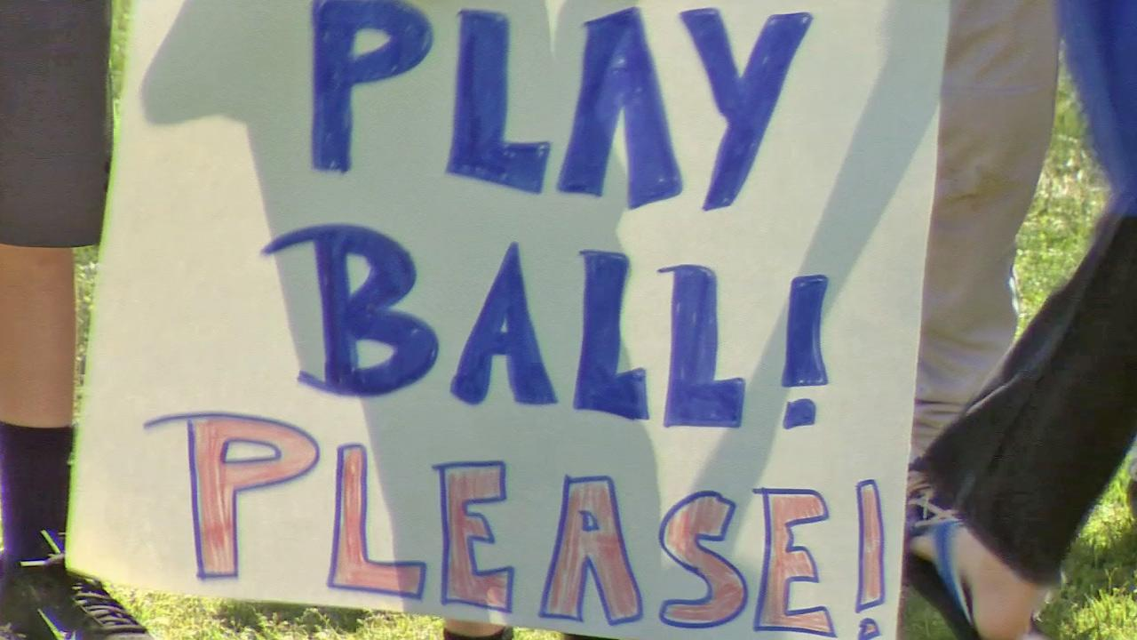 A player from the Newport Beach Little League holds a sign that reads, Play Ball! Please! on Sunday, March 16, 2014. All players in the league were suspended indefinitely March 12. The suspension was lifted March 16.