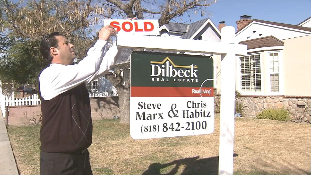 Real estate broker Chris Habitz modifies a sign on a property that was just sold on Tuesday, Jan. 15, 2013.