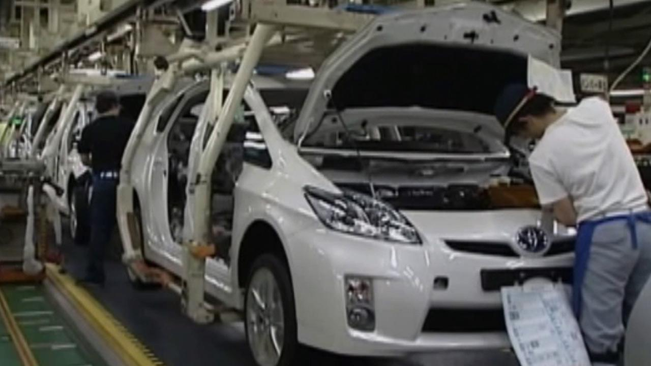 An employee works on a Toyota Prius vehicle in this undated file photo.