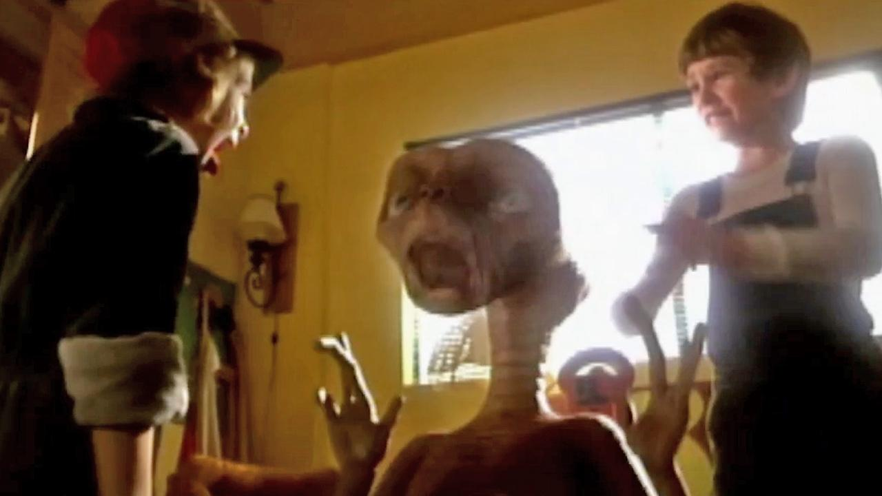 A still from footage of E.T.: The Extra-Terrestrial shows character Gertie, played by a young Drew Barrymore (left),  screaming as she first encounters an alien named E.T. (center) as introduced by her brother Elliot, played by Henry Thomas (right).