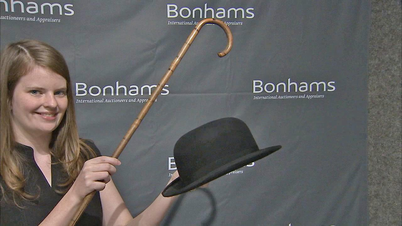 A woman is seen holding Charlie Chaplins hat and cane. The items fetched $62,500 total at an auction on Sunday, Nov. 18, 2012.