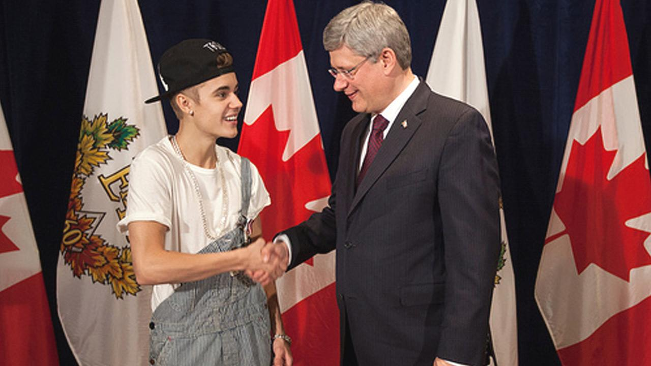 Justin Bieber and Canadian Prime Minister Stephen Harper shake hands after Bieber was awarded the Queen Elizabeth II Diamond Jubilee Medal.