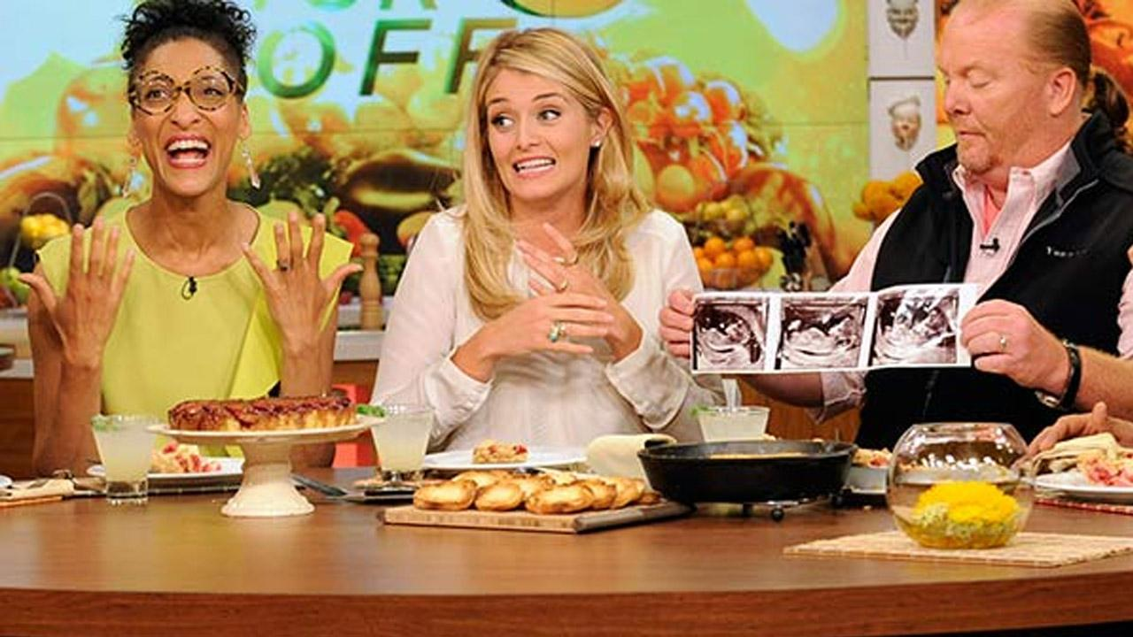 This image released by ABC shows co-hosts, from left, Carla Hall, Daphne Oz and Mario Batali holding three sonogram images, at a taping of the daytime series The Chew, on Thursday, Sept. 5, 2013, in New York.