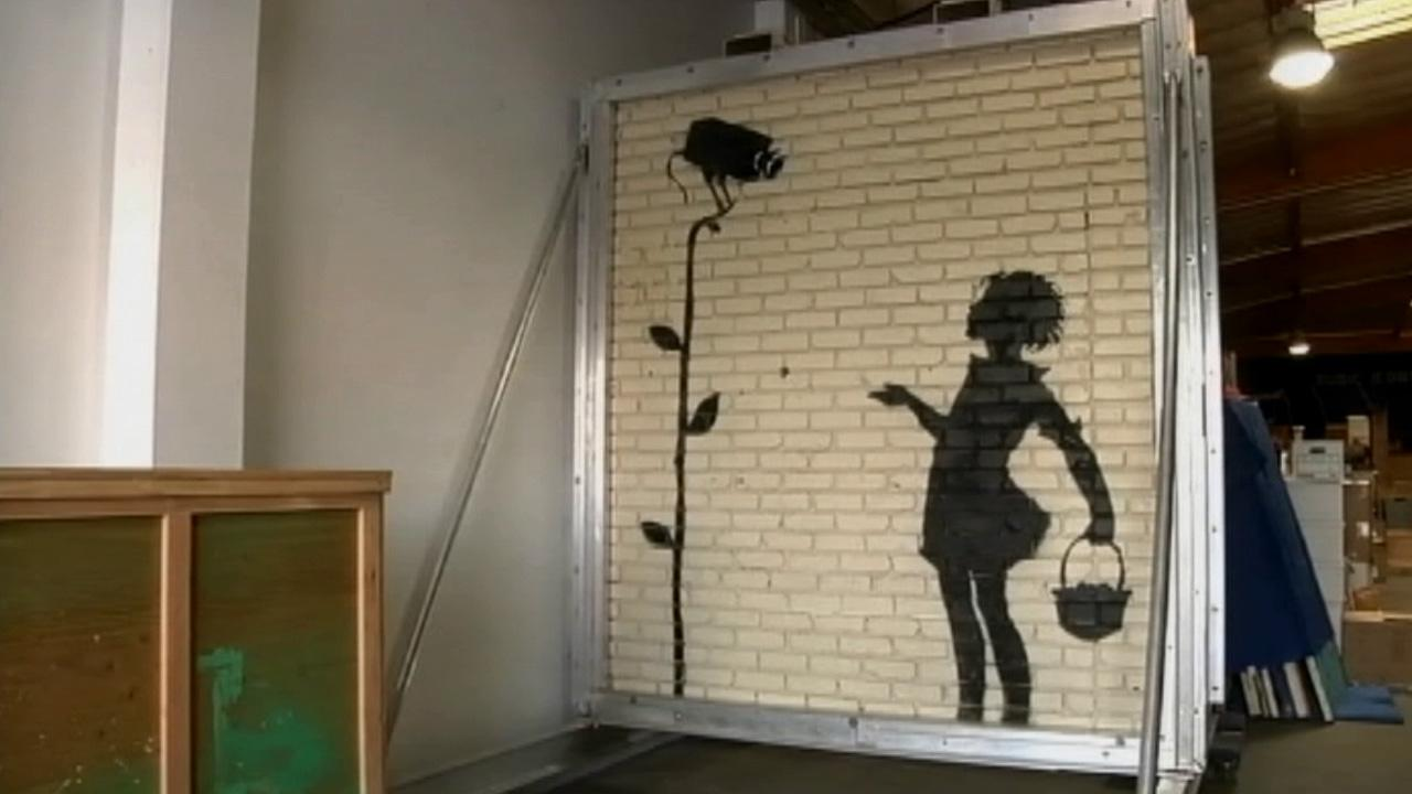 The mural titled Flower Girl by the anonymous street artist Banksy is seen in this undated photo. The piece was painted on a 9x8 foot section of brick wall at a gas station in Hollywood in 2008.