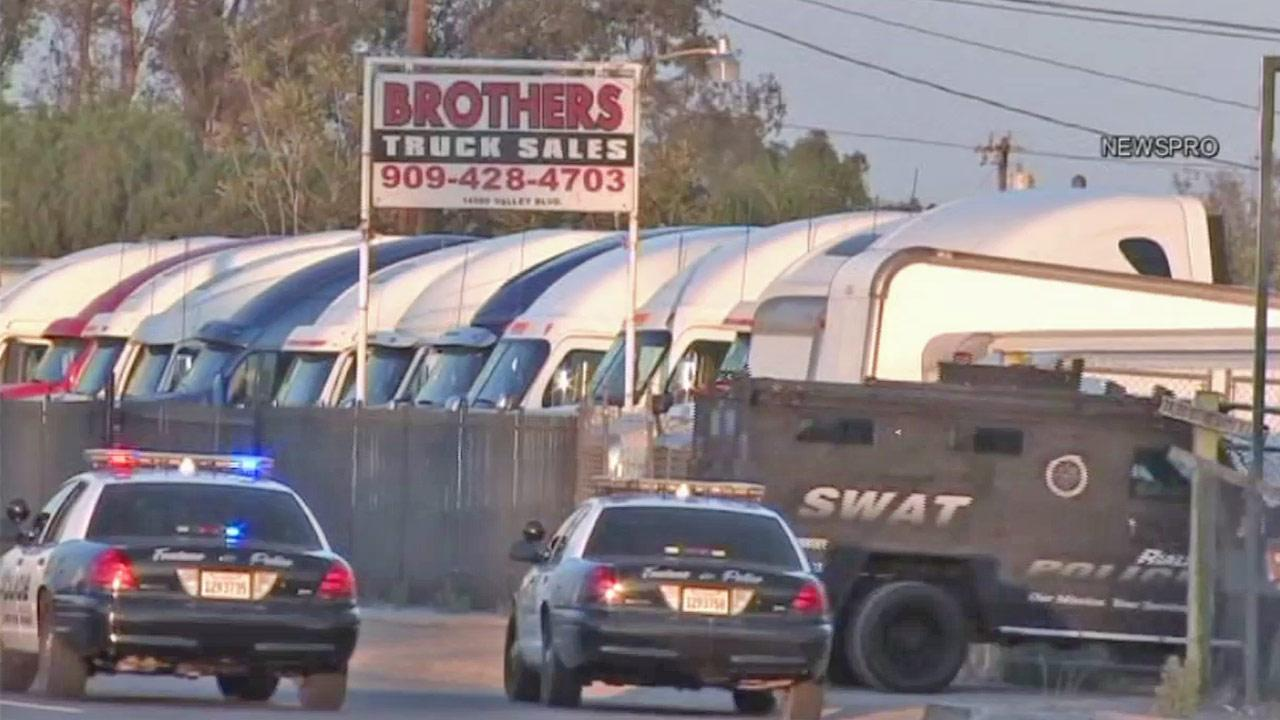 Fontana police patrol cars and a SWAT vehicle surround a trucking yard in Fontana on Saturday, July 14, 2012.