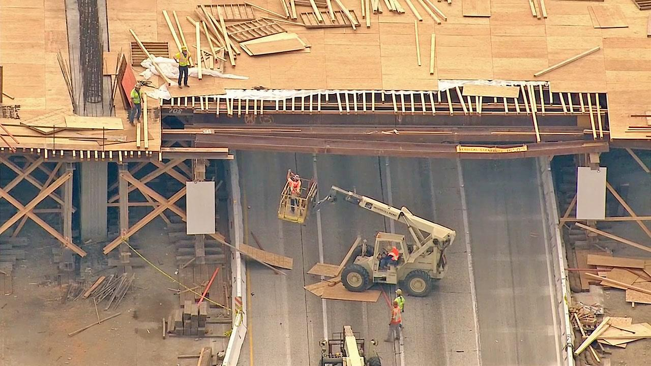 Crews are seen cleaning up after two trucks crashed into a bridge on the 10 Freeway in Fontana on Thursday, April 4, 2013.