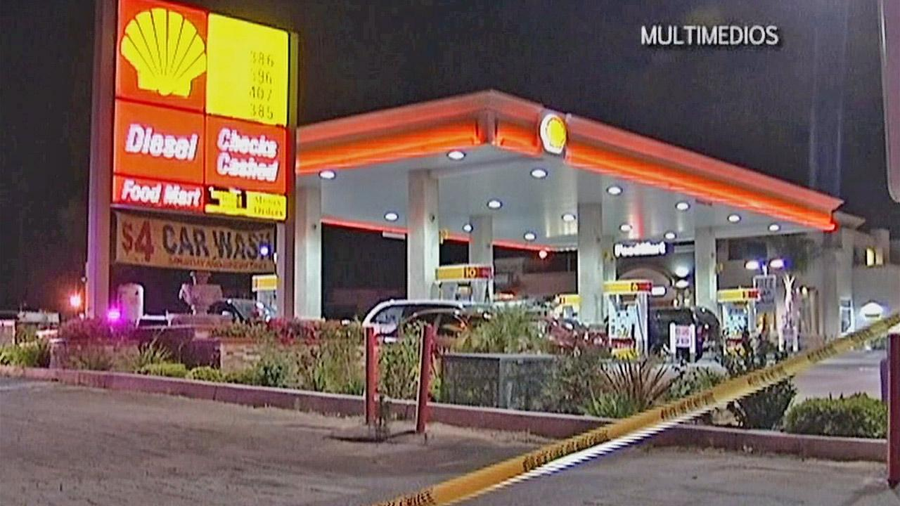 Police are seen at a gas station in Colton where a corrections officer was shot Thursday, May 2, 2013. The officers condition is unknown.
