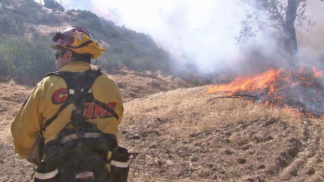 A firefighter works to put out the Summit Fire in Banning in this April 2013 photo.