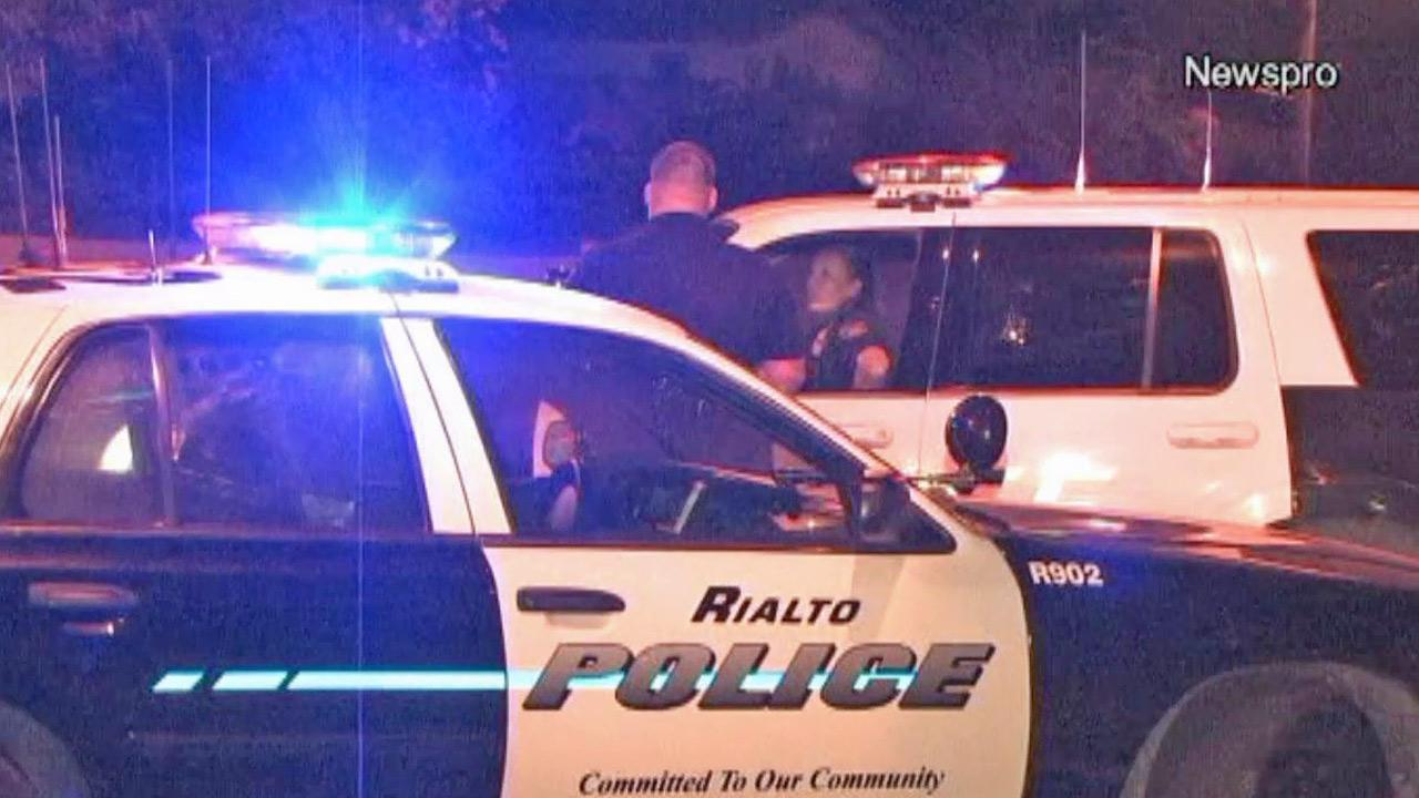 Rialto police officers assist San Bernardino police in searching for a gunman who opened fire on an officer on Friday, Aug. 2, 2013. The officer was not hit.