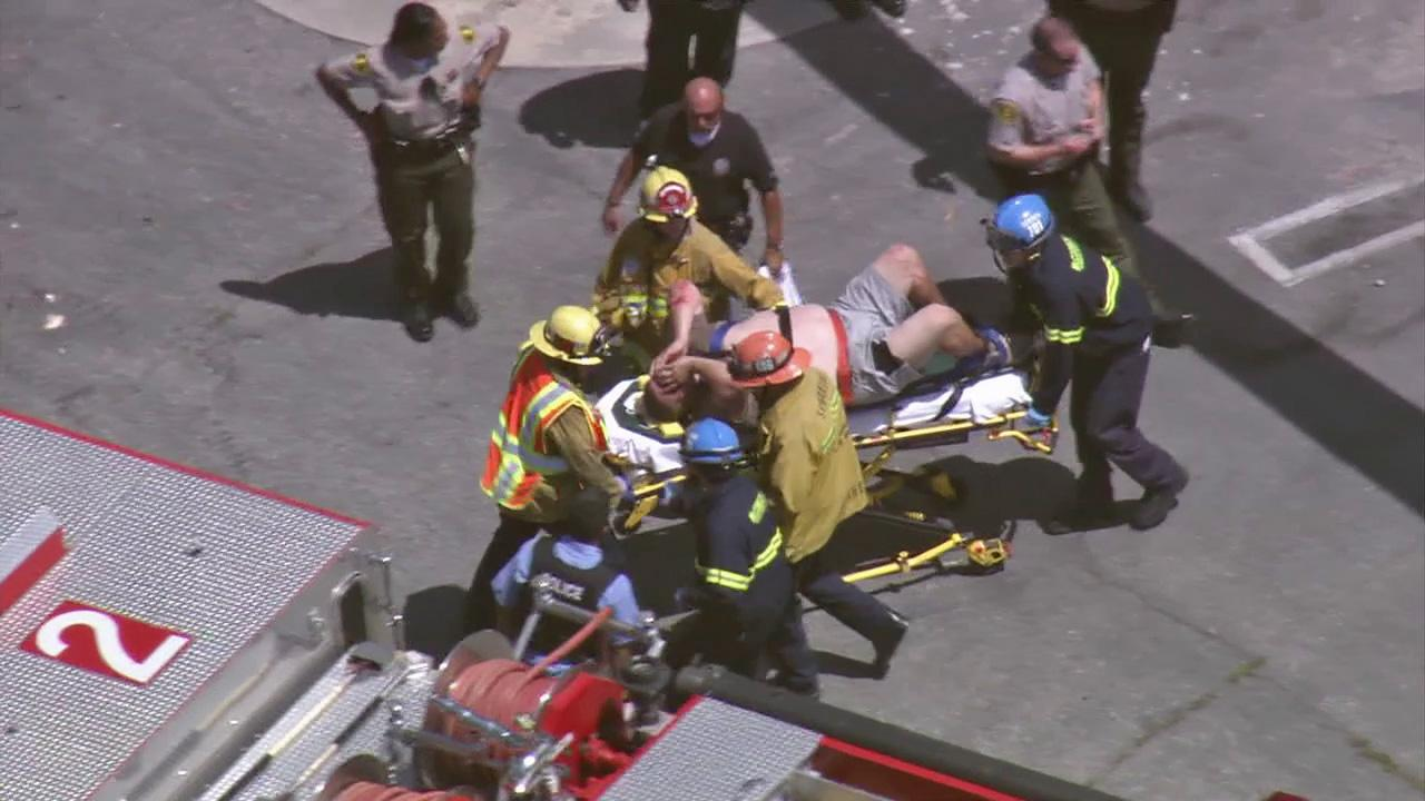 A pursuit suspect is put on a stretcher after the man drove off an embankment and slammed into a tree in Rolling Hills Estates during a high speed chase on Tuesday, July 10, 2012.