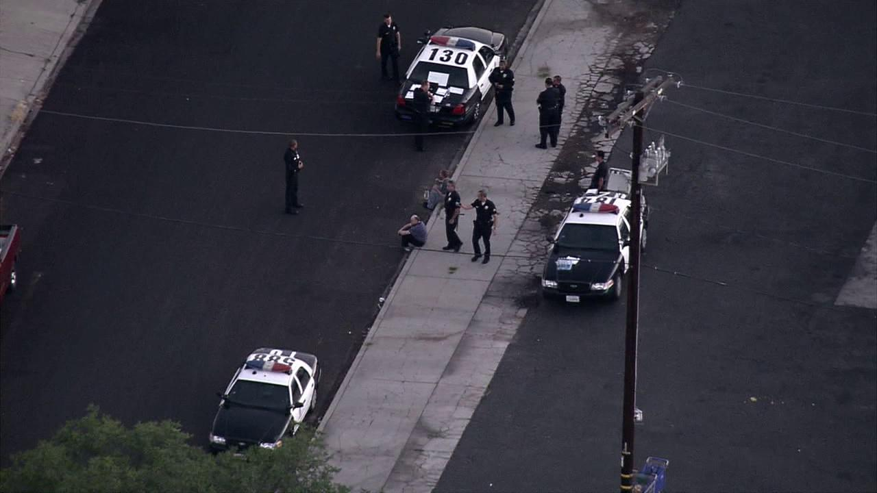 Police officers stand at the scene of an officer-involved shooting in Reseda on Thursday, July 19, 2012.
