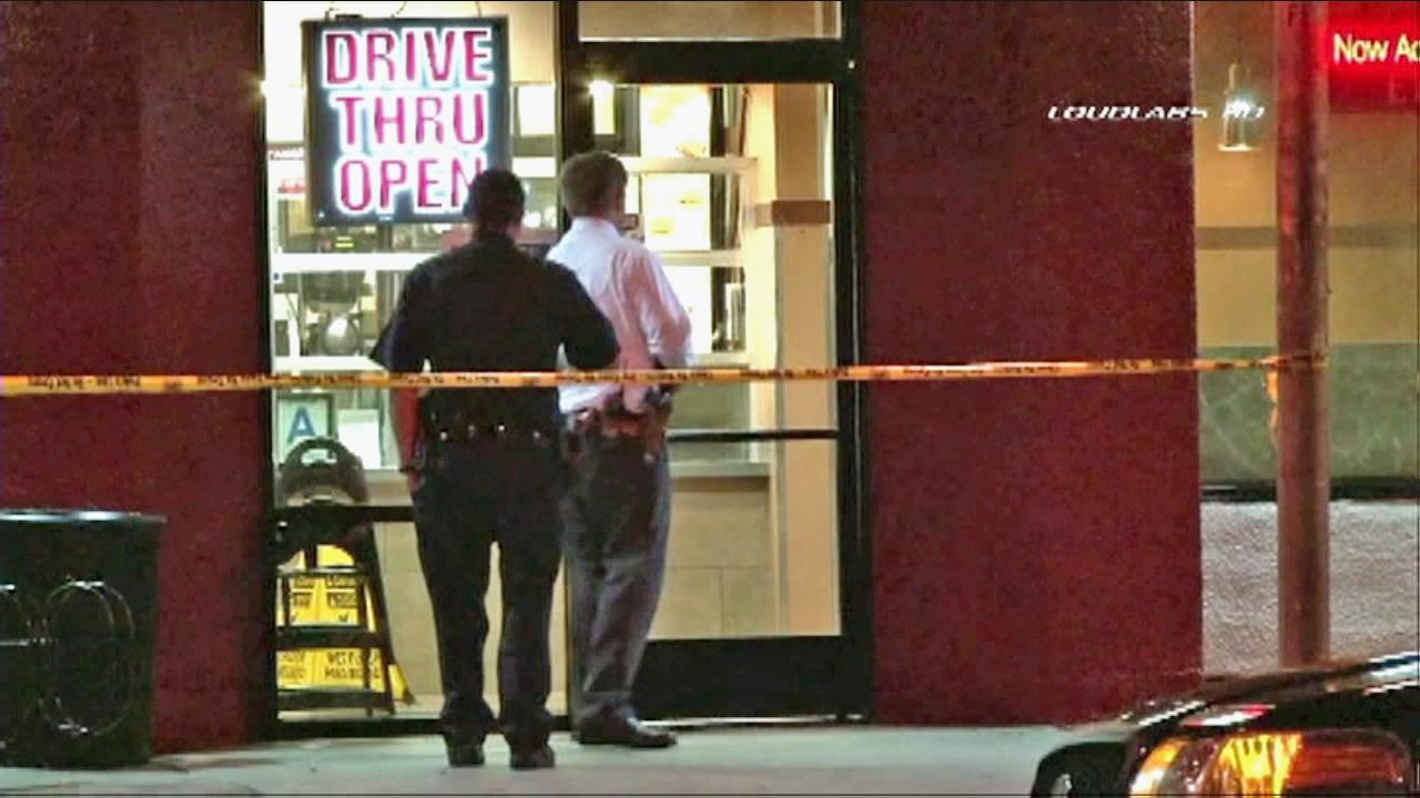 Detectives investigate the scene after a stabbing victim collapses in the drive-thru lane of Jack in the Box in South Los Angeles on Wednesday, Aug. 1, 2012.