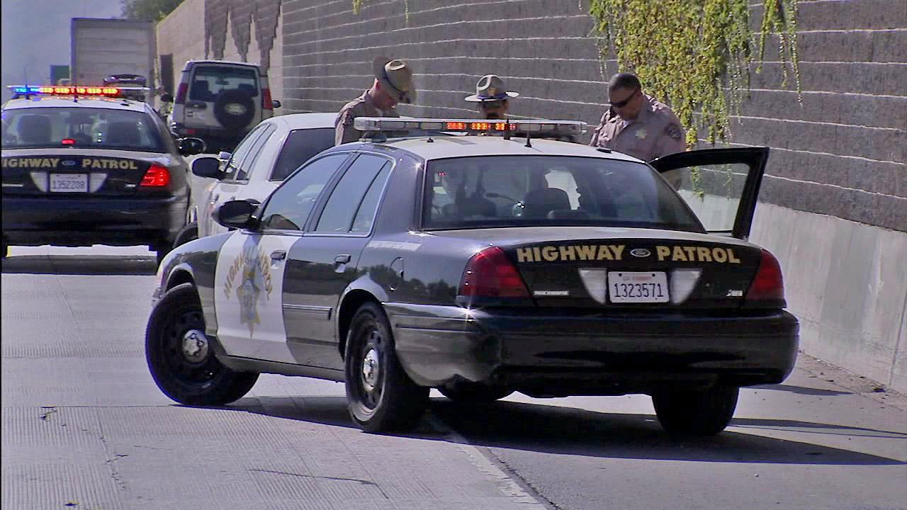CHP officers are seen at the site of an officer-involved shooting that shut down the westbound 60 Freeway at Hacienda Boulevard on Saturday, August 4, 2012.