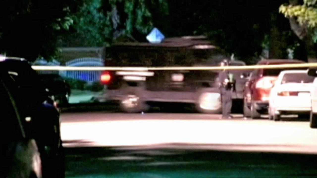 A law enforcement vehicle is shown driving behind police tape at the scene of a standoff in North Hollywood.