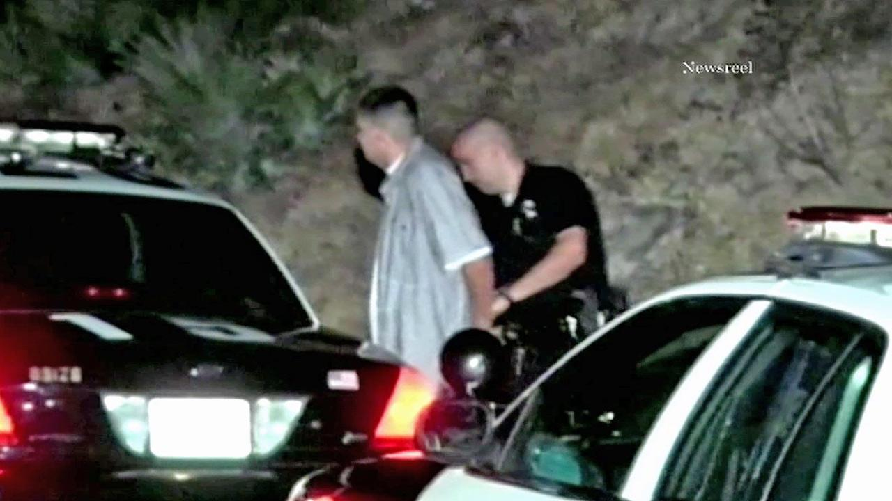 A man is shown being detained by law enforcement for allegedly pointing a laser at airplanes.