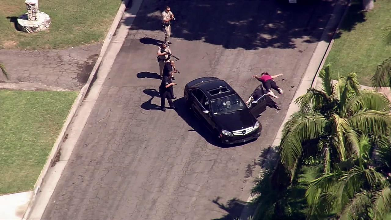 Police ordered a pursuit suspect and a woman who ran out of a nearby house to get on the ground at the end of a high-speed chase on Friday, Sept. 7, 2012.