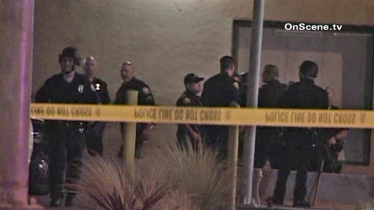 Police are shown behind crime scene tape near a Long Beach apartment complex, where gunshots were reported on Friday, Sept. 14, 2012.