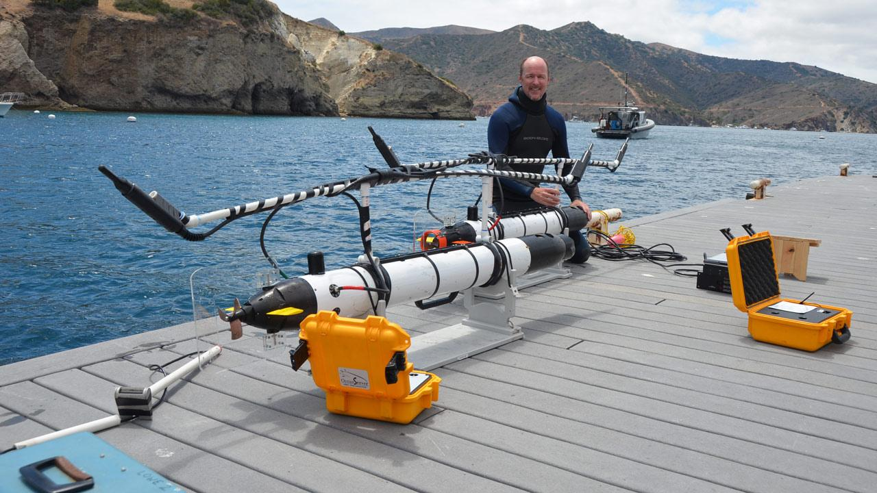 Dr. Chris Lowe, a marine biologist at Cal State Long Beach, is seen with two of his shark-tracking robots off Catalina Island in July 2012.