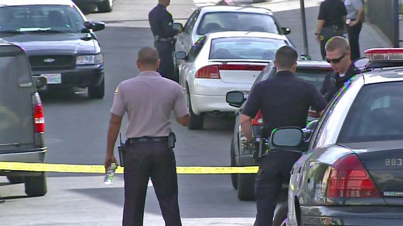 Investigators surround the scene of an officer-involved shooting in the Jefferson Park area on Saturday, Oct. 6, 2012.