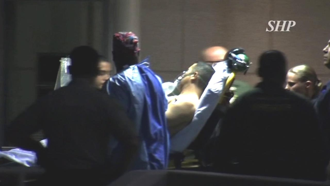 A Los Angeles County sheriffs deputy is wheeled away on a stretcher after he was shot while trying to detain a group of reported gang members in the Florence area of South Los Angeles on Friday, Nov. 16, 2012.