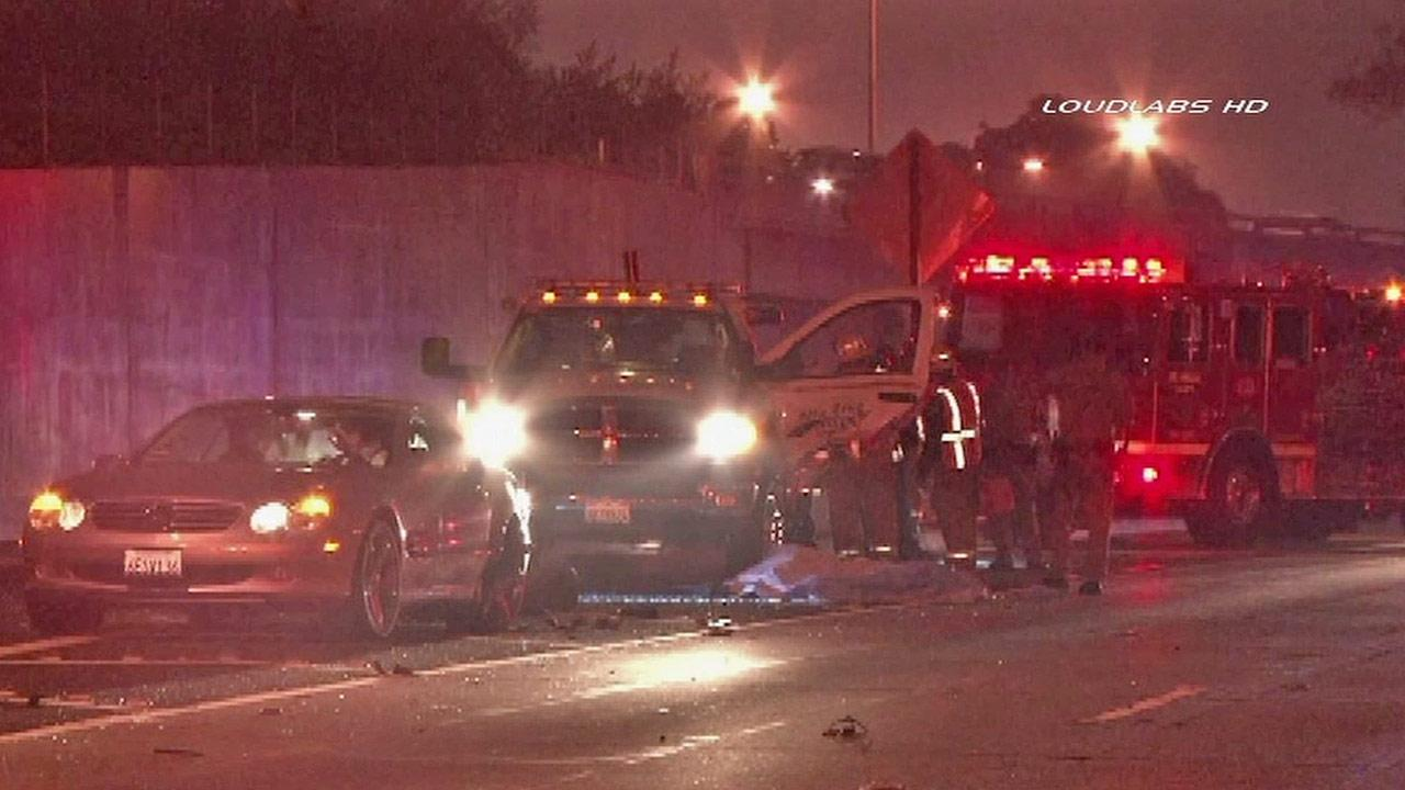 Firefighters are shown at the scene of a crash where a tow truck driver was struck by a passing car and killed in Signal Hill on Sunday, Dec. 9, 2012.