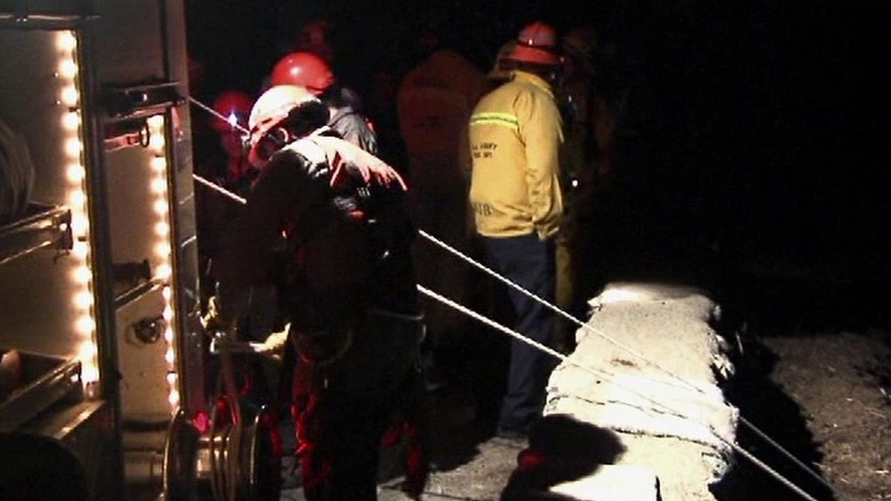 Officials are seen rescuing a man whose car plummeted 300 feet off a mountain road north of Glendora on Wednesday, Dec. 20, 2012.