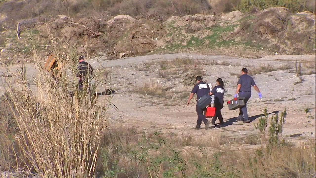 Investigators are seen near Big Tujunga Canyon Road where human remains were found on Saturday, Jan. 19, 2013.