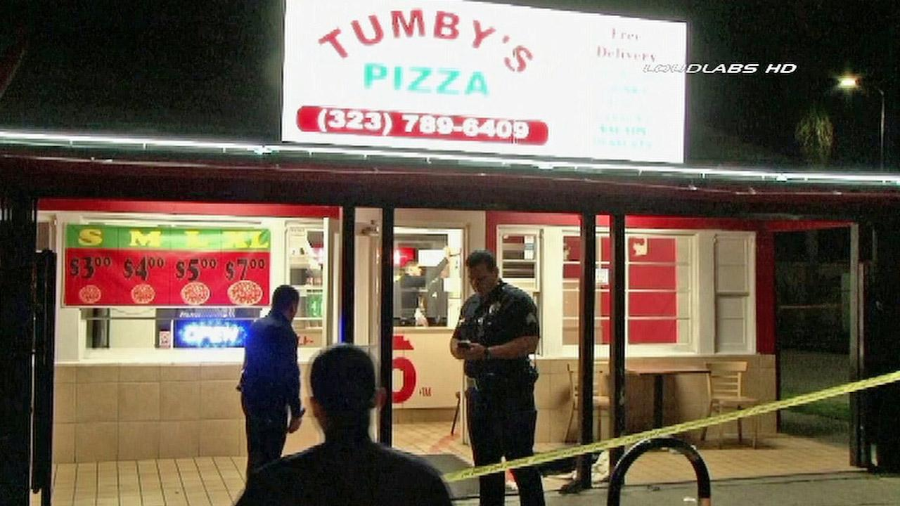 Investigators are shown outside of Tumbys Pizza in South Los Angeles following a fatal shooting on Thursday, Jan. 31, 2013.