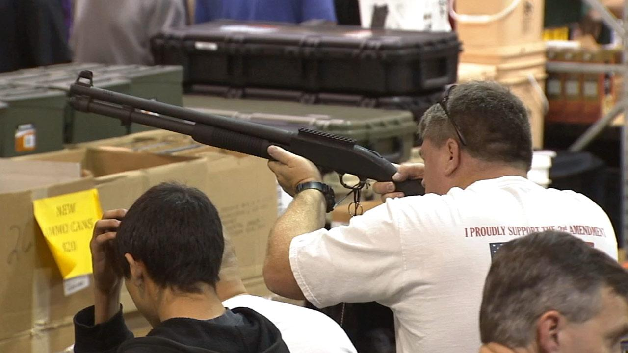 A man looks down the sight of a shotgun at the Glendale Gun Show on Saturday, March 2, 2013.
