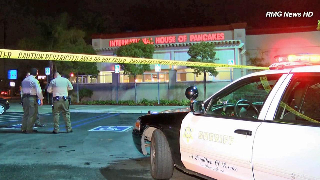 Crime tape ropes off the parking lot of an IHOP restaurant in Rosemead, where a man was allegedly stabbed by a pair of hitchhikers he picked up in Arizona.