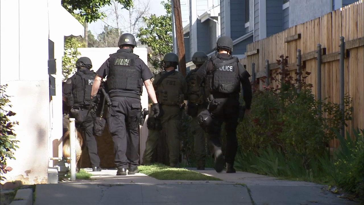 Officers are seen searching for two suspects who opened fire on deputies in Pasadena on Thursday, March 14, 2013.