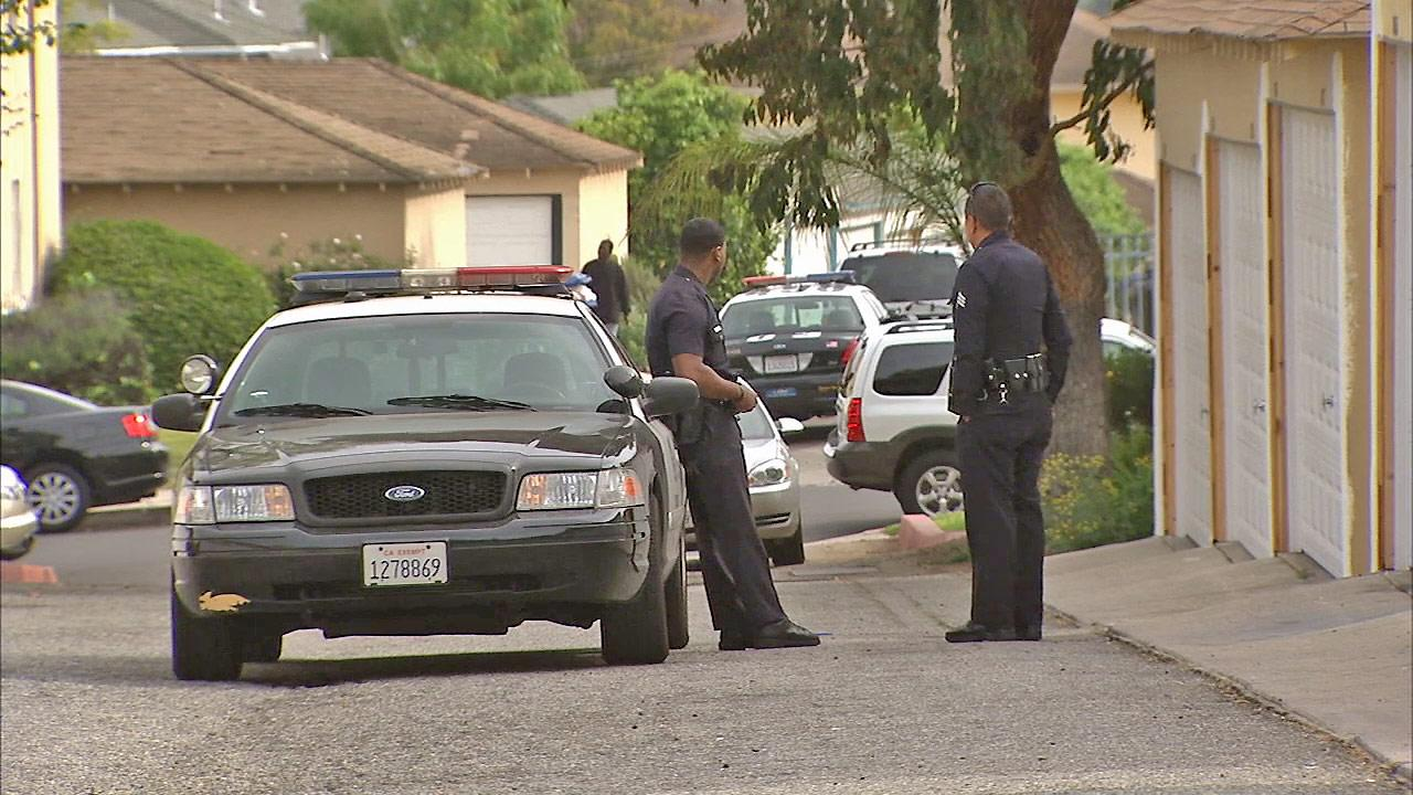 Police officers are seen at an apartment building in the Crenshaw District of Los Angeles, where a man was found shot to death on Sunday, April 7, 2013.