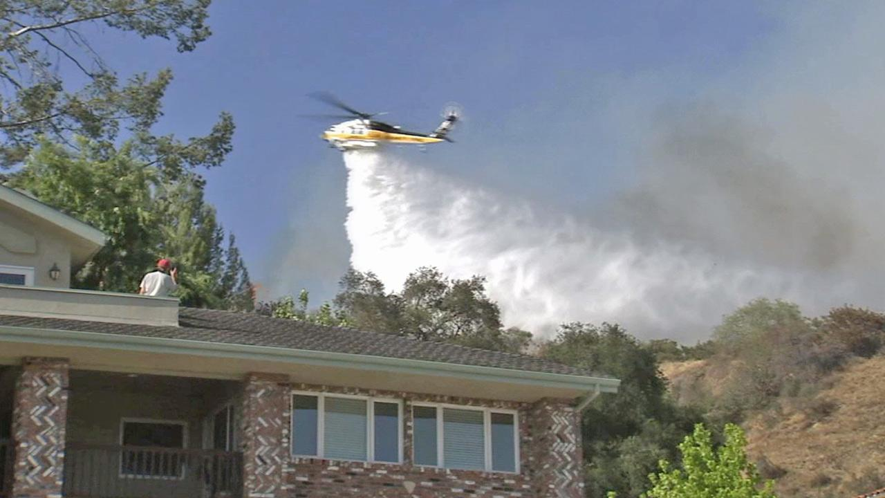 A helicopter drops water on a brush fire in Monrovia on Saturday, April 20, 2013.