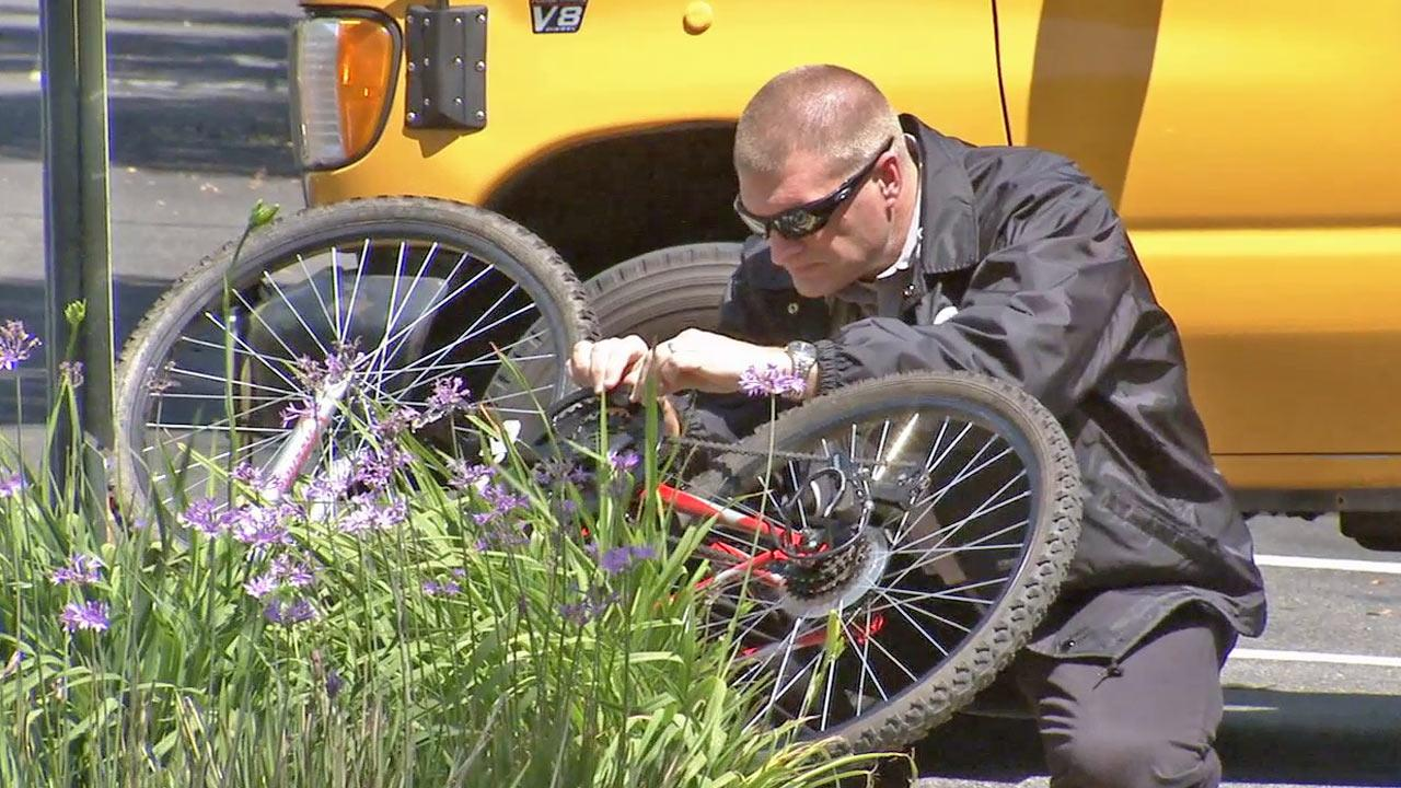 A law enforcement official inspects a bicycle that was involved in a fatal bus crash in at the intersection of Columbus Avenue and Riverdale Drive in Glendale on Thursday, May 2, 2013.