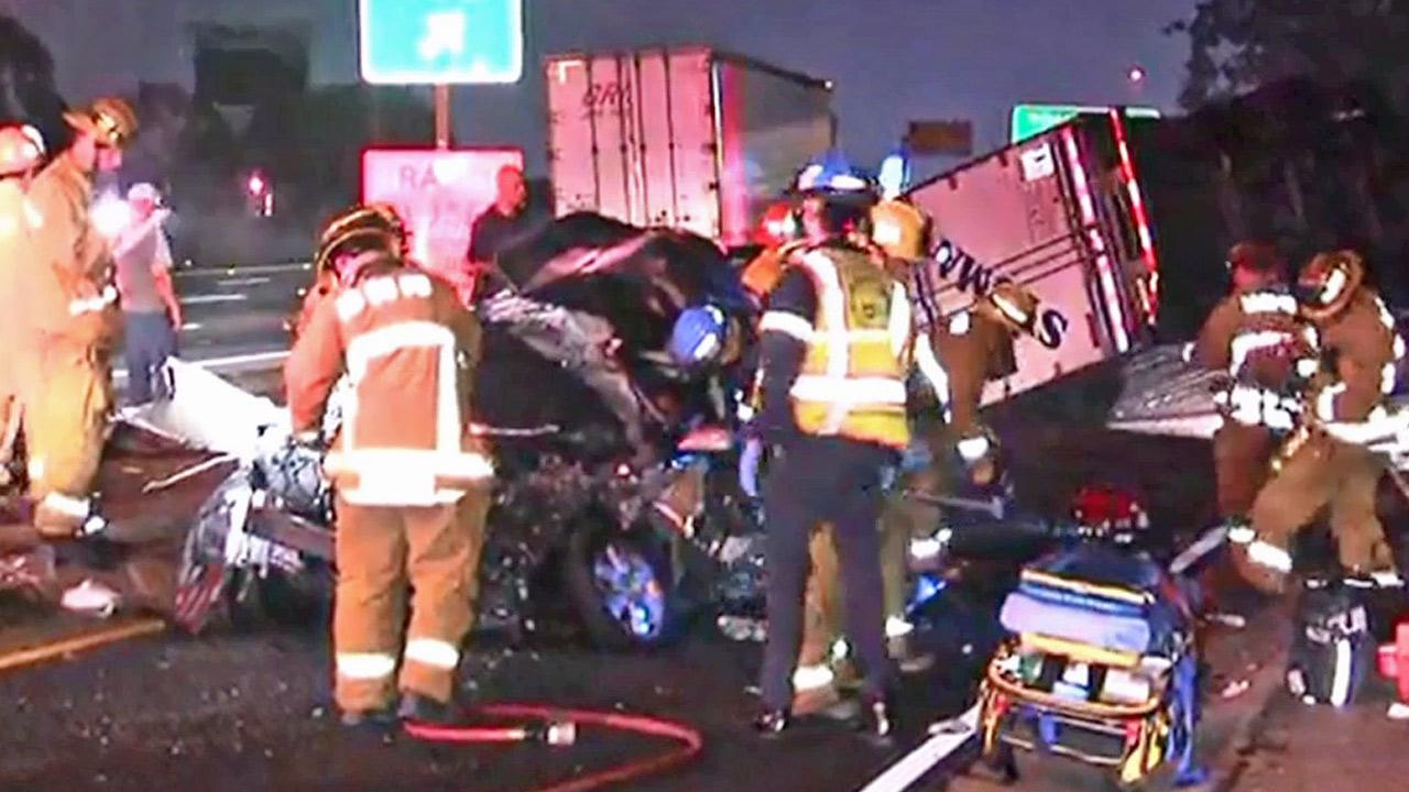 Emergency officials are shown at the scene of a crash involving a big rig and a stalled car on the southbound 405 Freeway in Hawthorne on Friday, June 28, 2013.