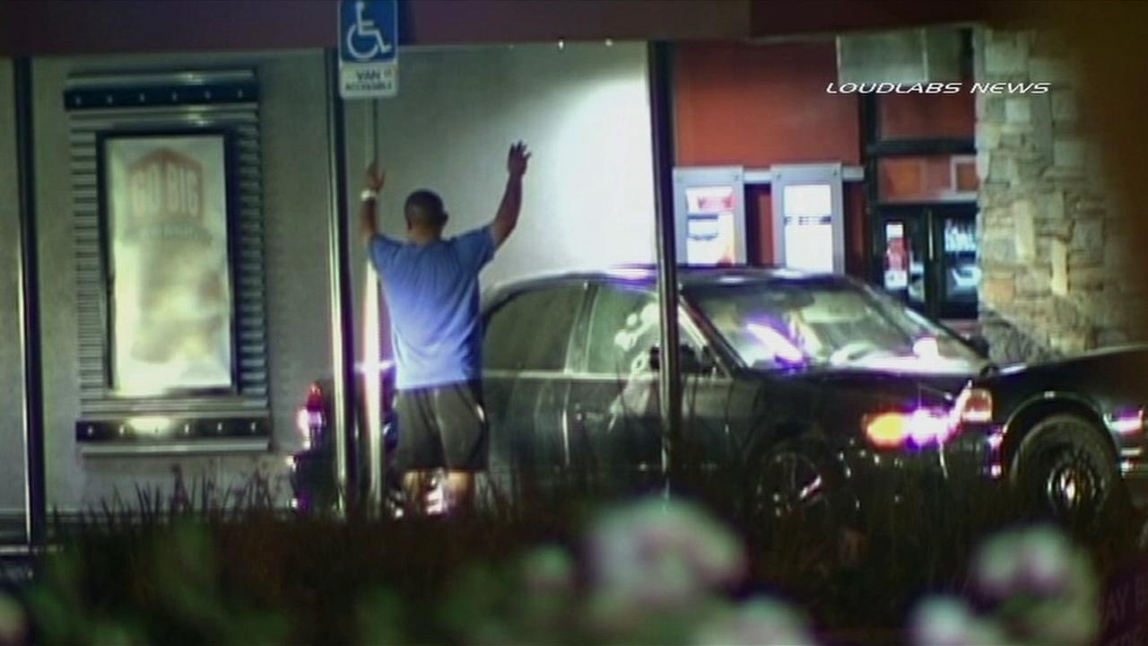 A man is seen with his hands in the air after a standoff in the drive-thru of the Jack in the Box at Telegraph and Carmenita roads in Santa Fe Springs on Thursday, July 4, 2013.