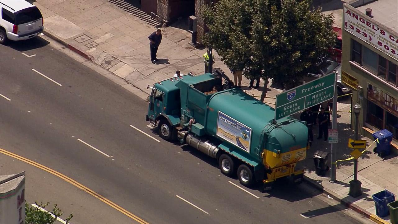 Police investigate after a city trash truck struck and killed a woman in the Lincoln Heights area on Monday, July 22, 2013.