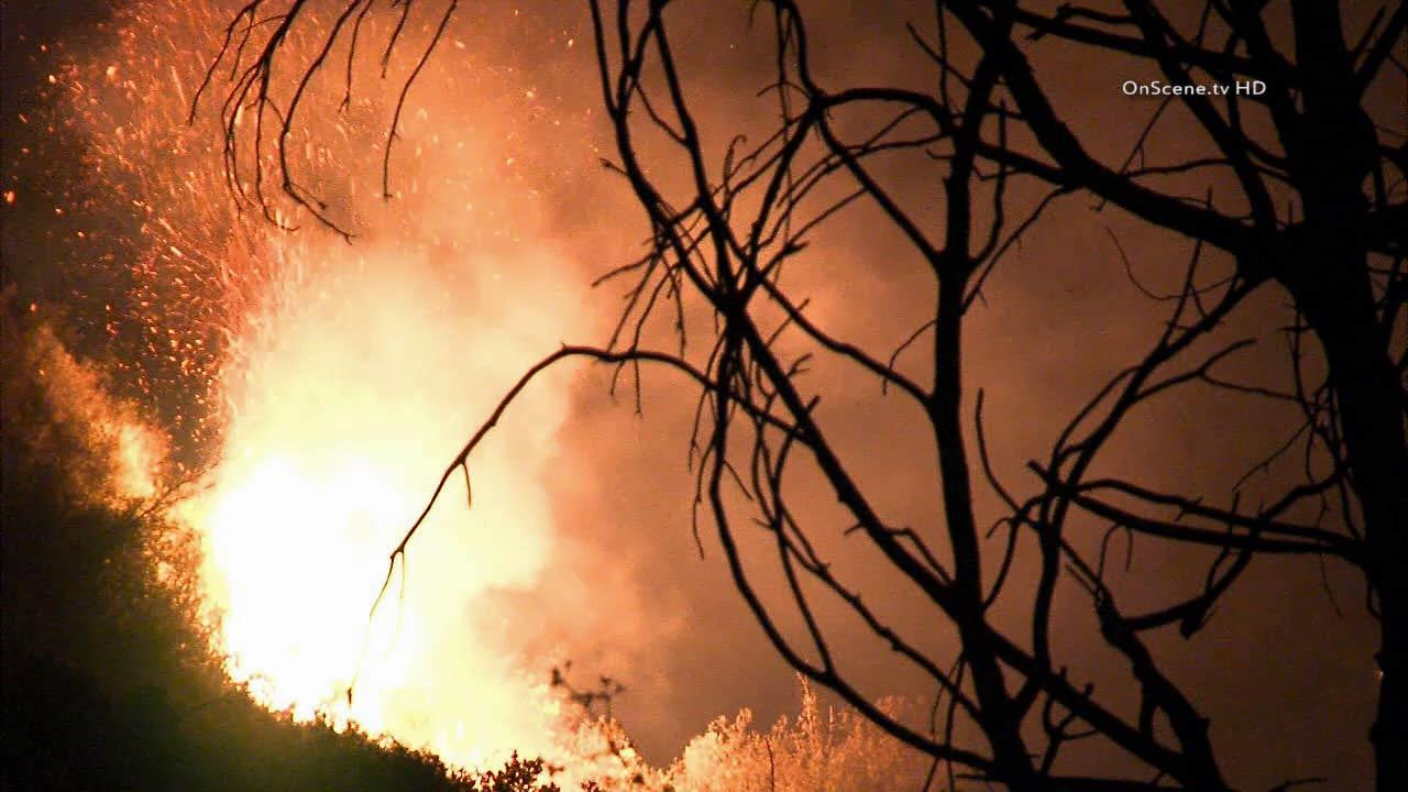 A man was killed and a woman injured in a vehicle crash that sparked a small brush fire in the Angeles National Forest on Friday, August 16, 2013.