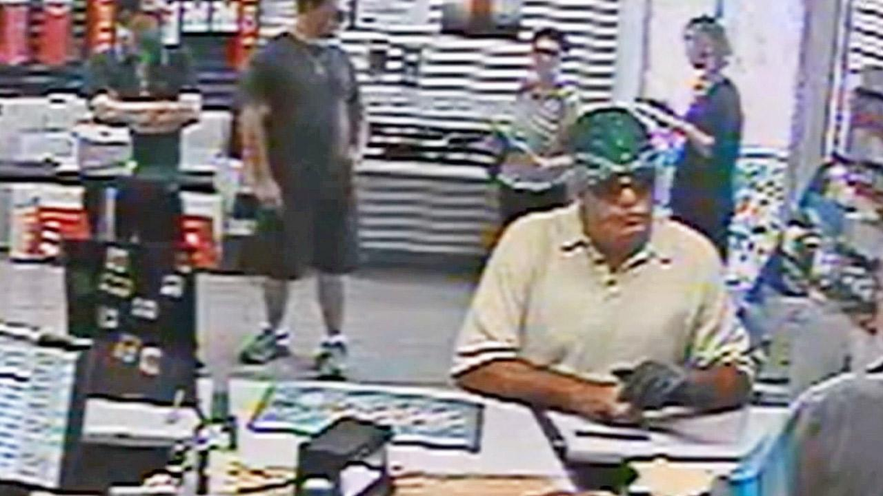 A surveillance image shows a suspect brandishing a gun and holding up a United States Postal Service clerk at a post office in Studio City on Wednesday, Sept. 18, 2013.