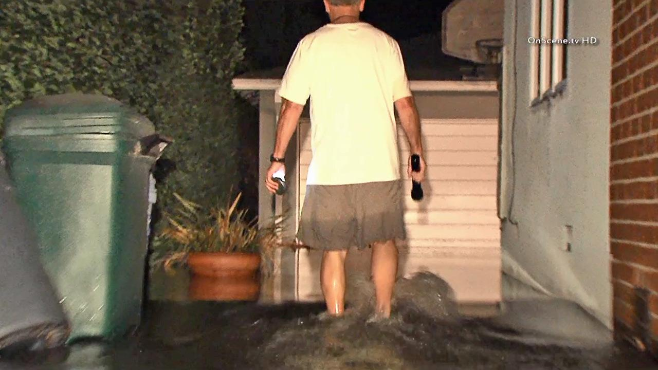 A man wades through water outside his Mar Vista home after a broken water main flooded a neighborhood on Saturday, Sept. 28, 2013.