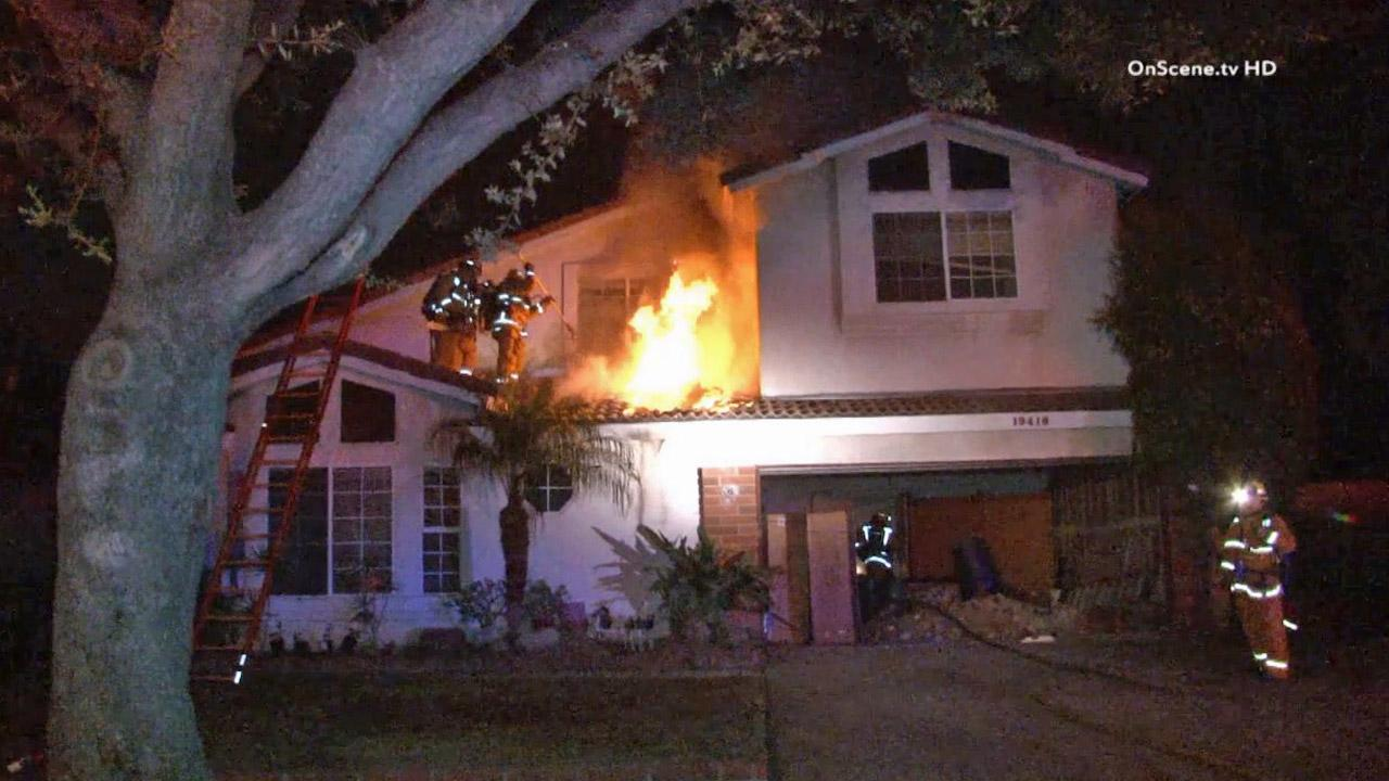 Firefighters work to put out a house fire in Cerritos in the 19400 block of Jacob Avenue on Thursday, Oct. 3, 2013.