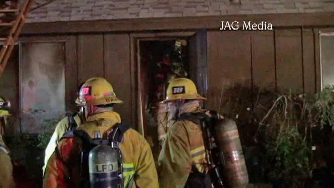 Firefighters at the scene of a house fire in Sylmar on Sunday, Oct. 20, 2013.