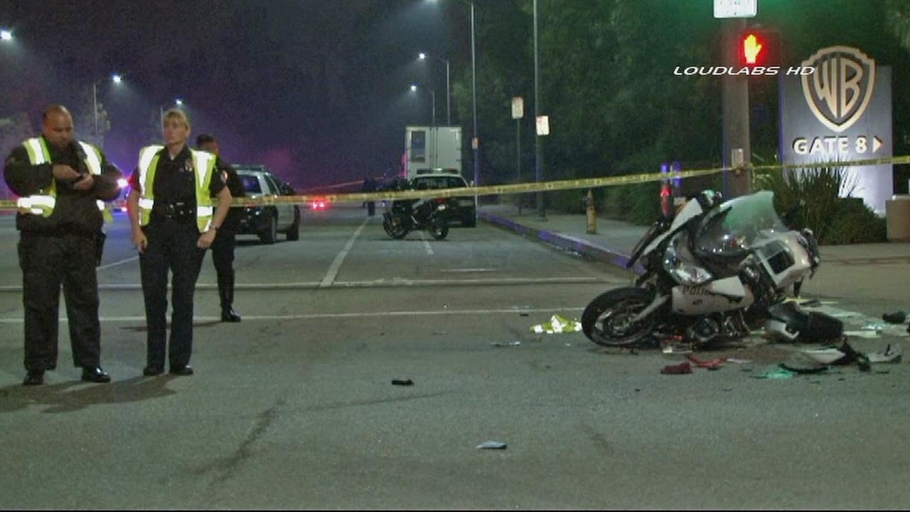 Police investigate an accident involving an LAPD motorcycle and a car at Forest Lawn Drive near Barham Boulevard in Los Angeles on Saturday, Oct. 26, 2013.