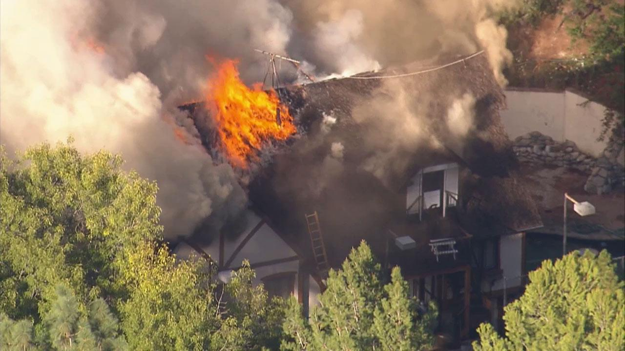 A fire burns at a mansion in Encino on Wednesday, Oct. 30, 2013.