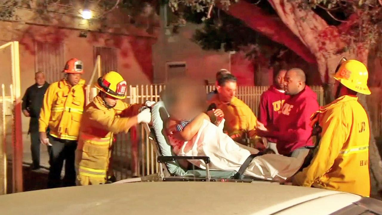 A victim is wheeled out of an apartment complex following a shooting at 106th Street and Central Avenue in Watts on Sunday, Nov. 10, 2013.