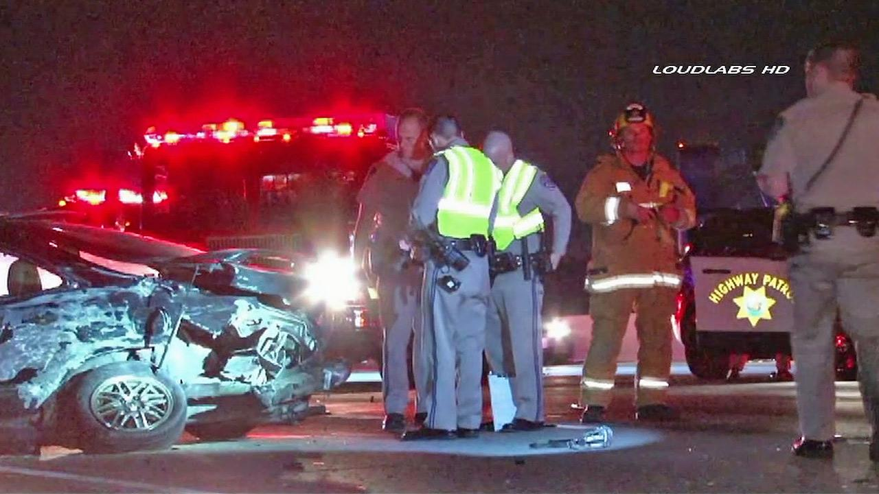 Authorities investigate the scene of a car crash on the 60 Freeway in Montebello that left one woman dead on Sunday, Dec. 15, 2013.