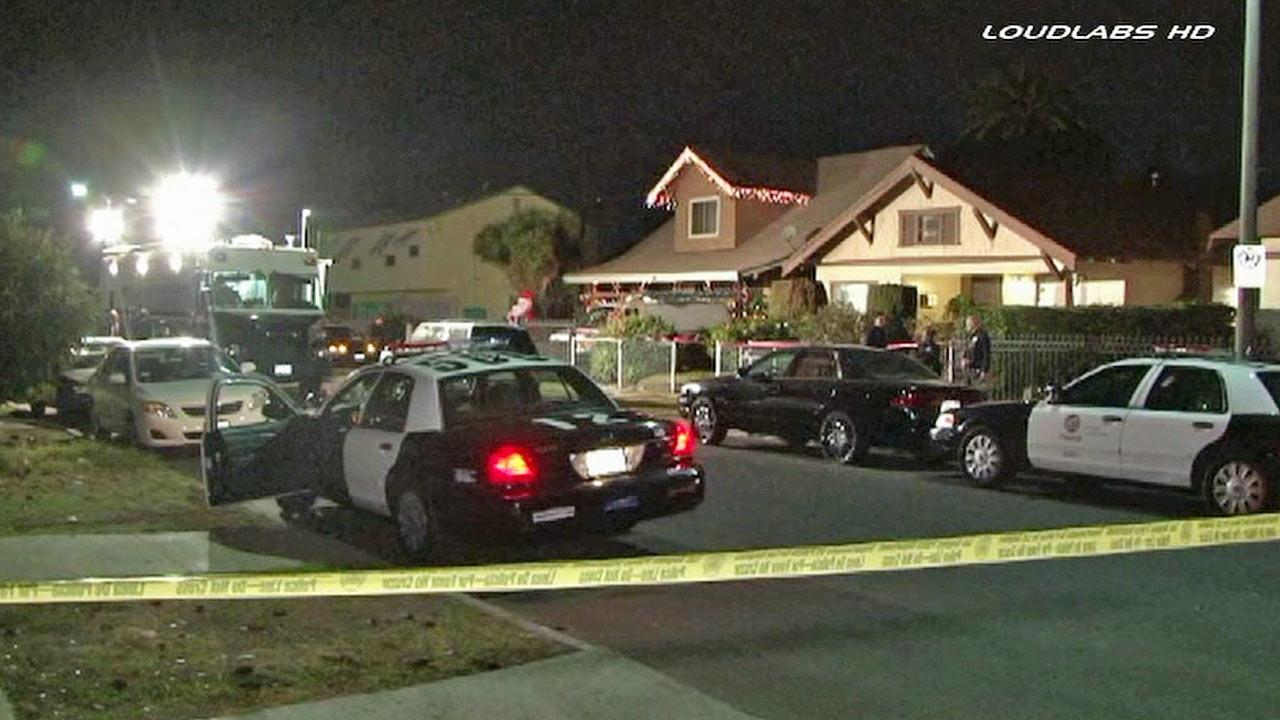 Police patrol vehicles are shown behind crime tape at the scene of an officer-involved shooting in the 1300 block of West 50th Street in South Los Angeles on Friday, Dec. 27, 2013.