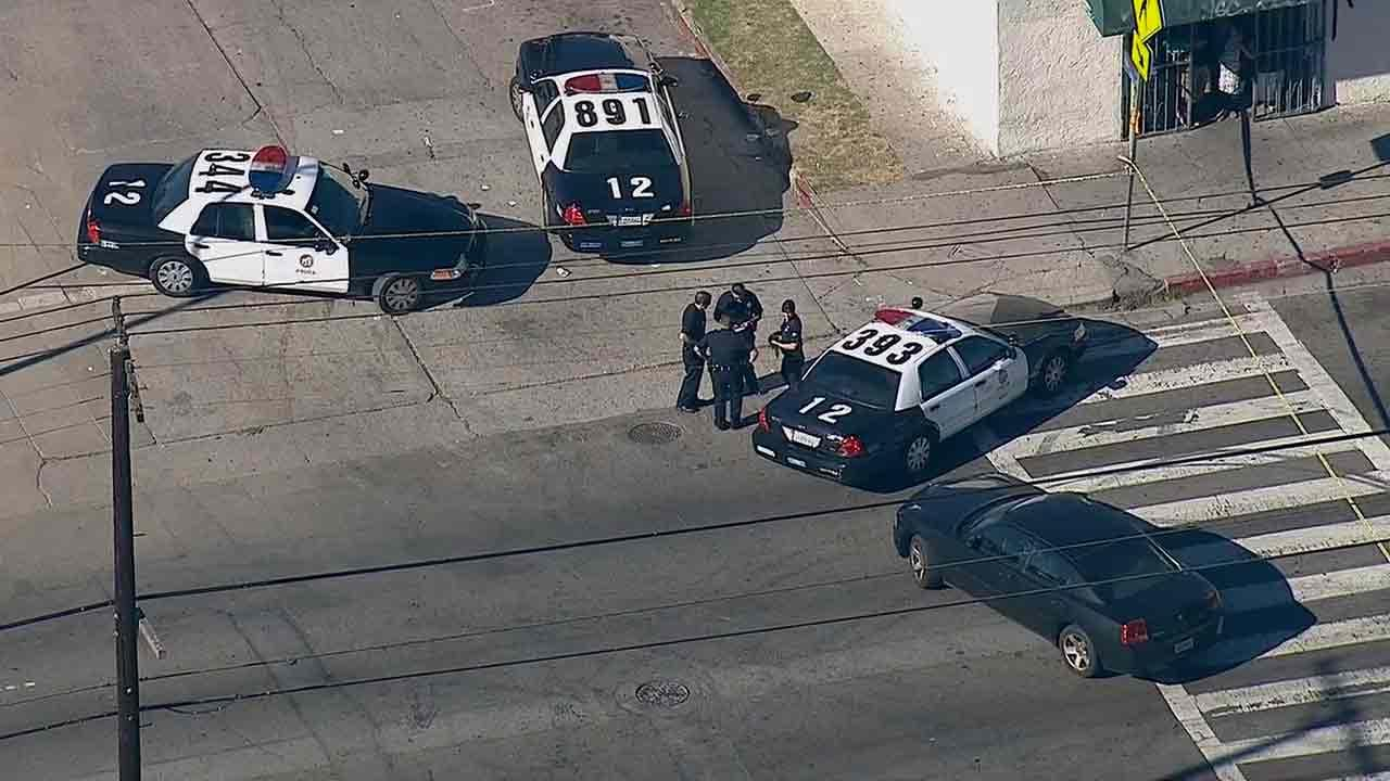 Police respond to the scene of a shooting near the intersection of 74th and Hoover streets in South Los Angeles Monday, Jan. 6, 2013.