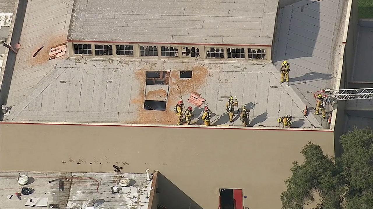 Firefighters are seen on the roof of a building at Roosevelt Middle School on Wednesday, Feb. 26, 2014.