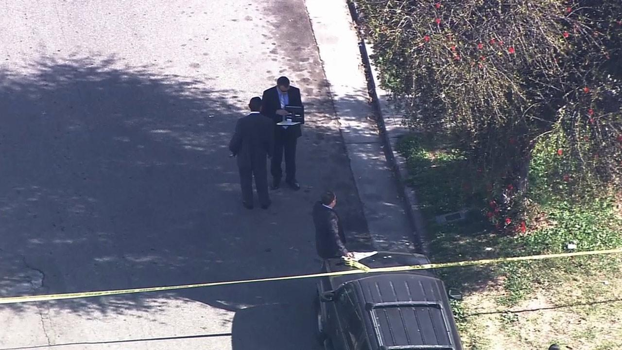 Detectives investigate a fatal shooting in South Los Angeles in the 5700 block of 9th Avenue on Monday, April 14, 2014.